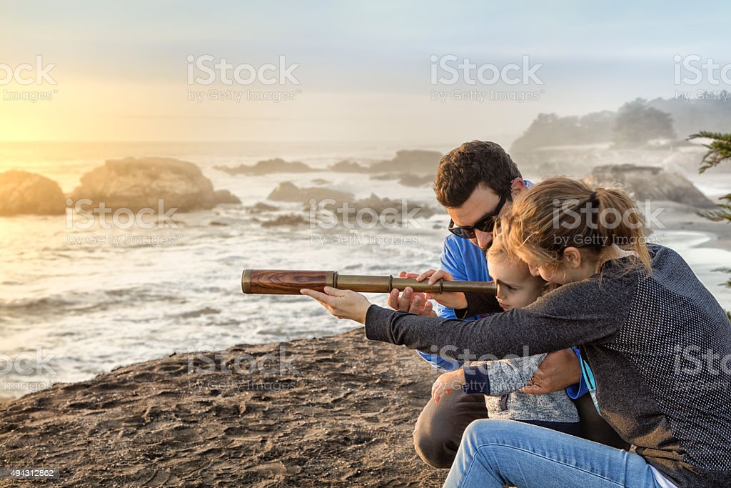 Family with spyglass looking toward ocean stock photo
