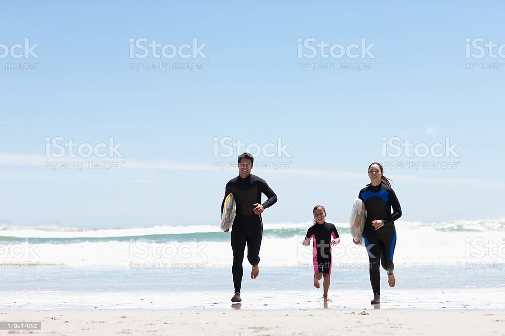 Family with surfboards running on beach royalty-free stock photo