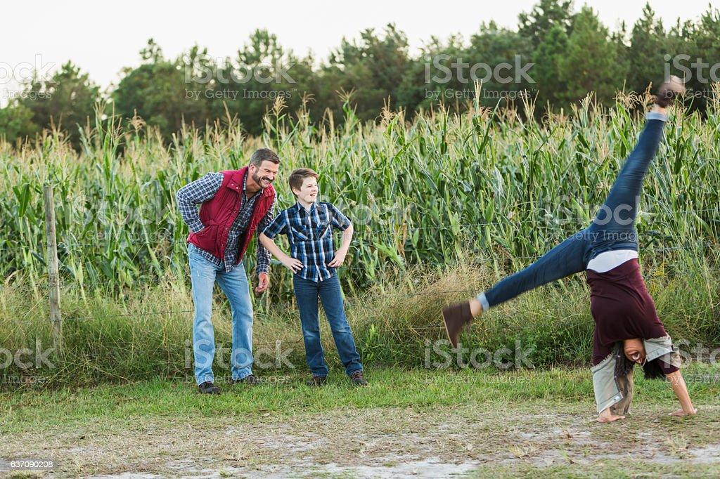 Family with teenage son on a farm, mom doing cartwheel stock photo