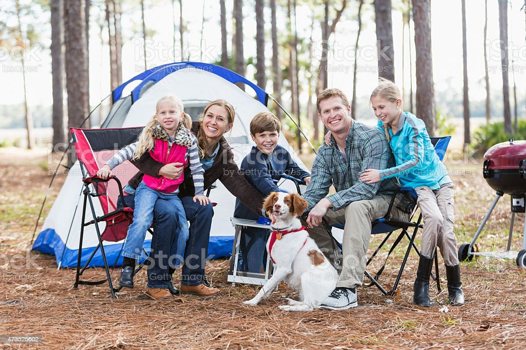 Family with three children and dog on a camping trip stock photo