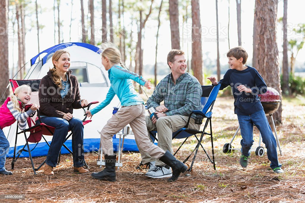 Family with three children having fun on camping trip stock photo