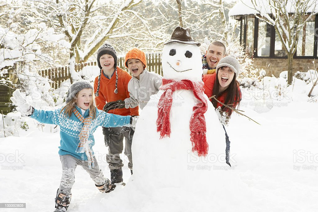 A family with two children building a snowman stock photo