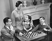 Family with two children (8-9) playing checkers (B&W), elevated view