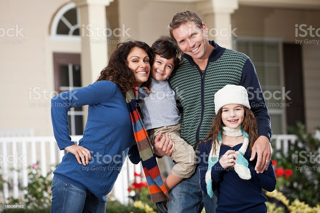 Family with two children standing in front of house royalty-free stock photo