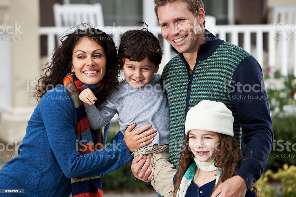 Family with two children standing in front of house stock photo