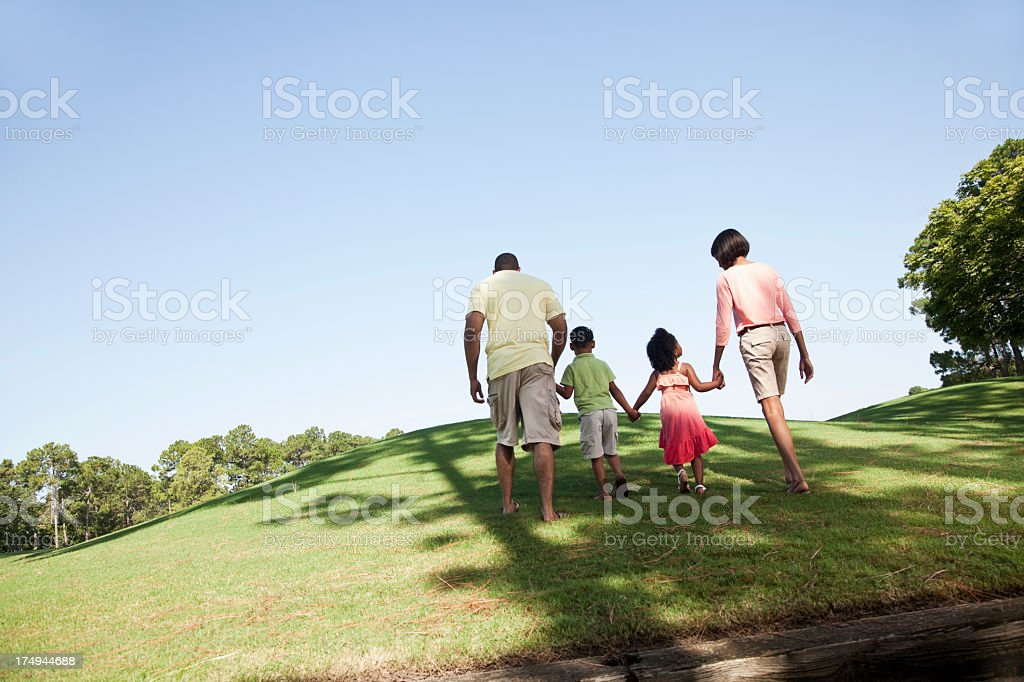 Family with two children walking up a hill royalty-free stock photo