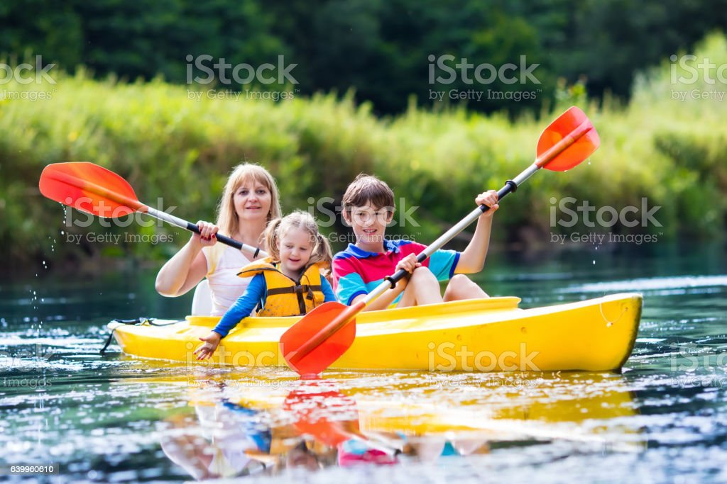 Family with two kids enjoying kayak ride on a river stock photo