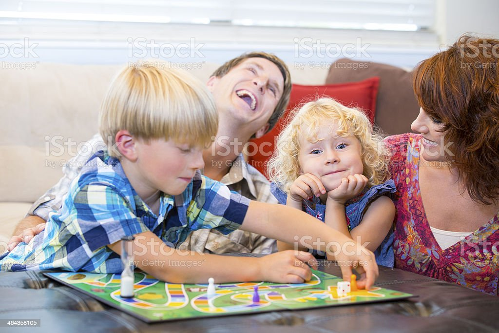Family with two kids having fun playing board games stock photo