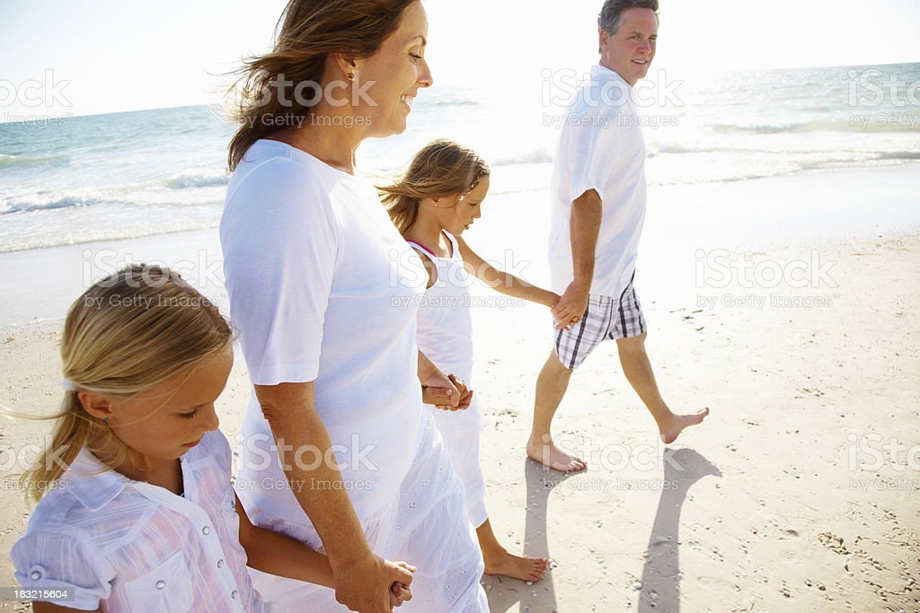 Family with two kids holding hands while walking on beach royalty-free stock photo