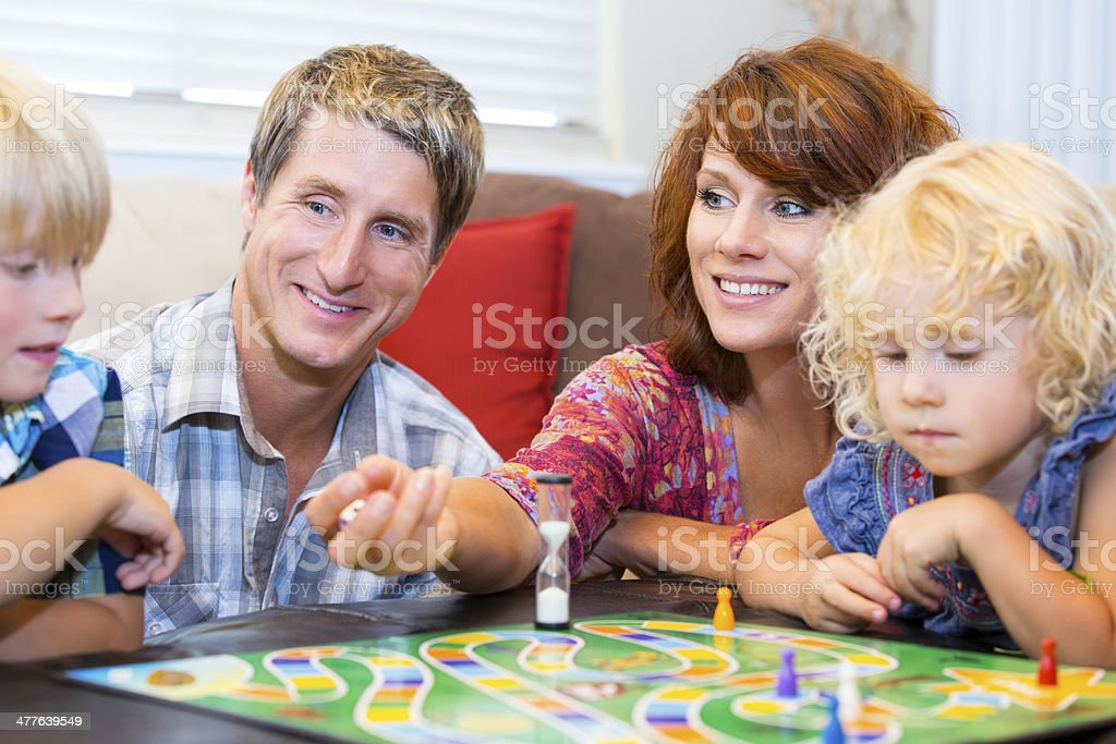 Family with two little kids having fun playing board games stock photo
