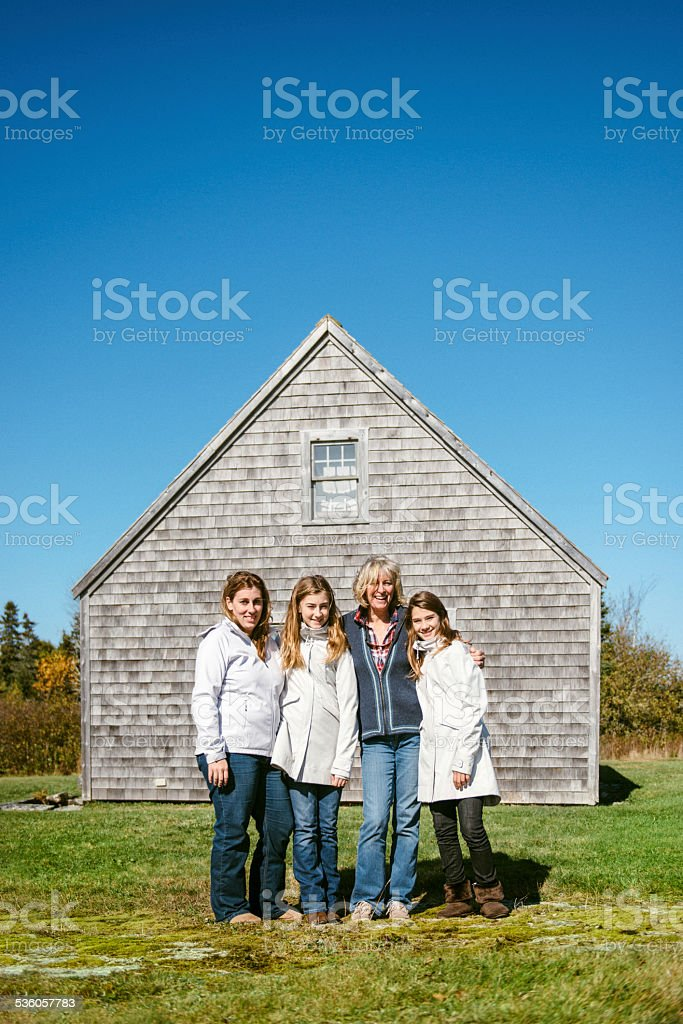 Family with two teenage children in front of summer cottage stock photo