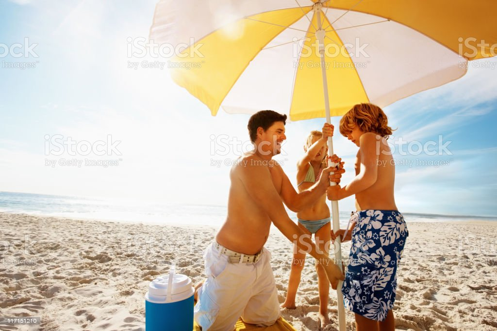 Family with umbrella at beach on a sunny day royalty-free stock photo