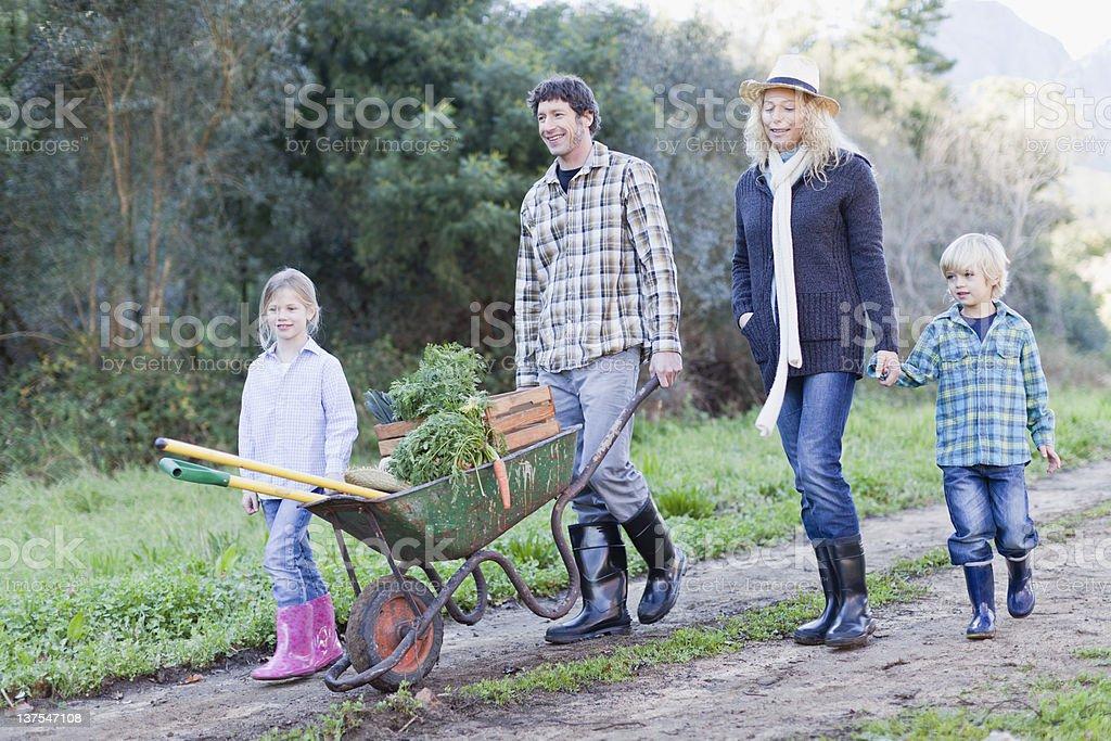 Family with wheelbarrow on dirt path stock photo