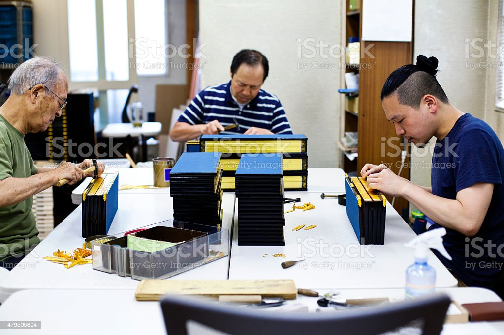 Family work on the wooden craft boxes, Tokyo. stock photo
