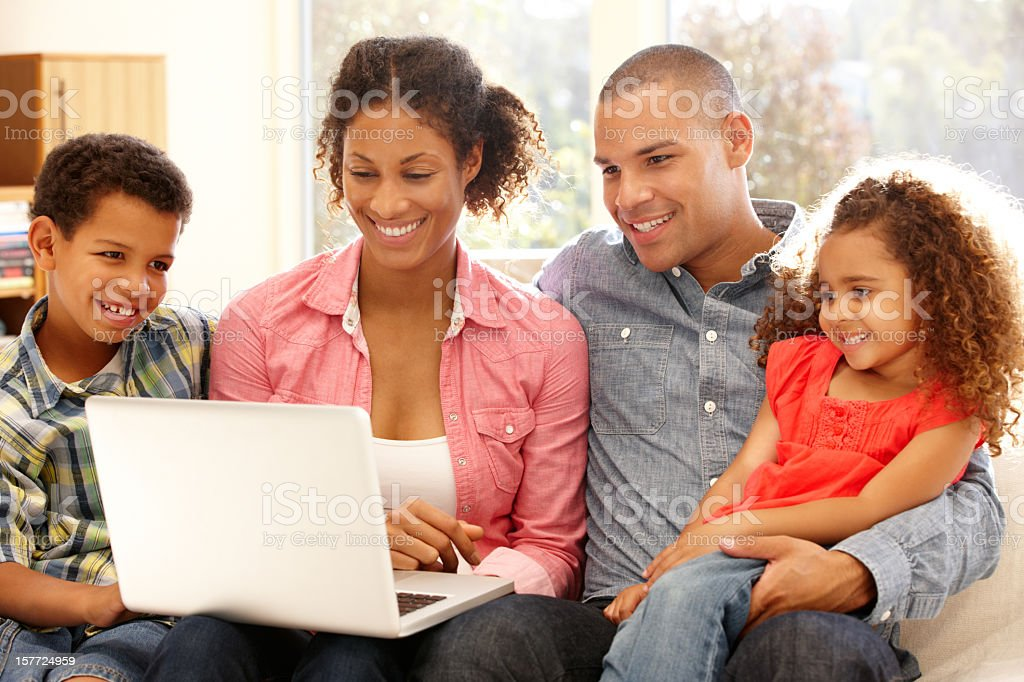 Family working on laptop at home stock photo