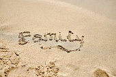'Family' written on sand beach background and texture