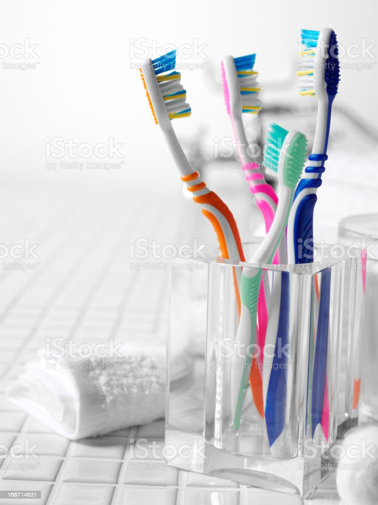 A family's colorful toothbrushes on tile stock photo