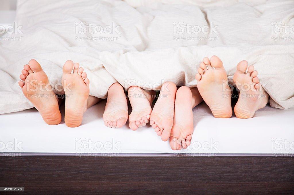 Family's feet hiding under blanket stock photo