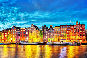 Famous Amstel river and night view of beautiful Amsterdam city.