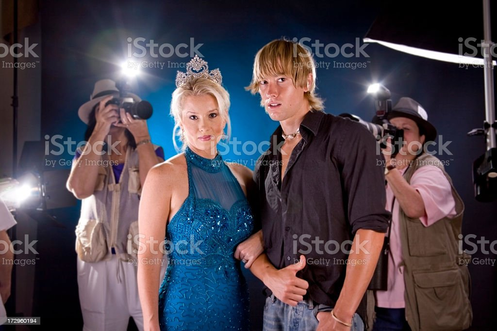 Famous celebrity with crown, escort. Paparazzi taking photographs. royalty-free stock photo