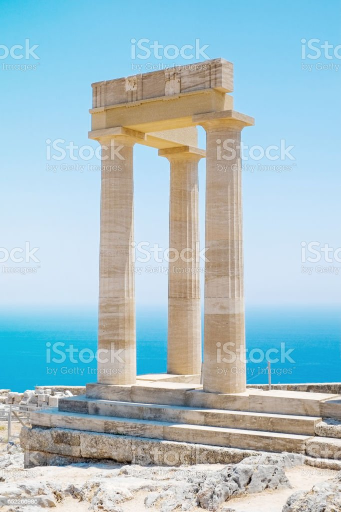 Famous Greek temple pillar against clear blue sky and sea in Lindos Acropolis Rhodes Athena Temple, Greece stock photo