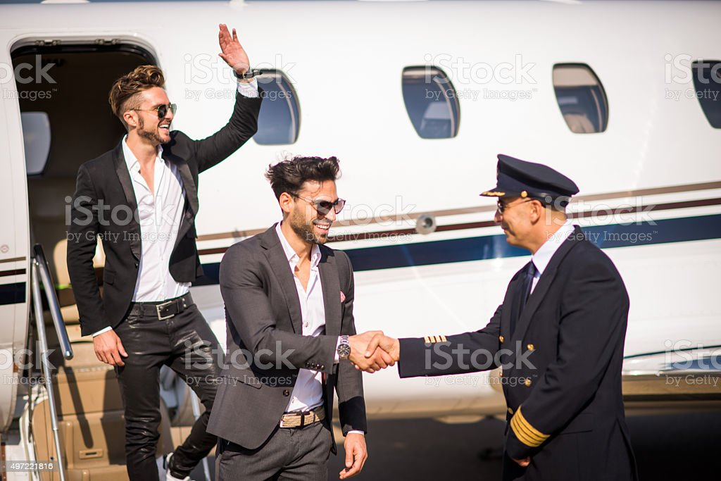 Famous men leaving private jet airplane stock photo