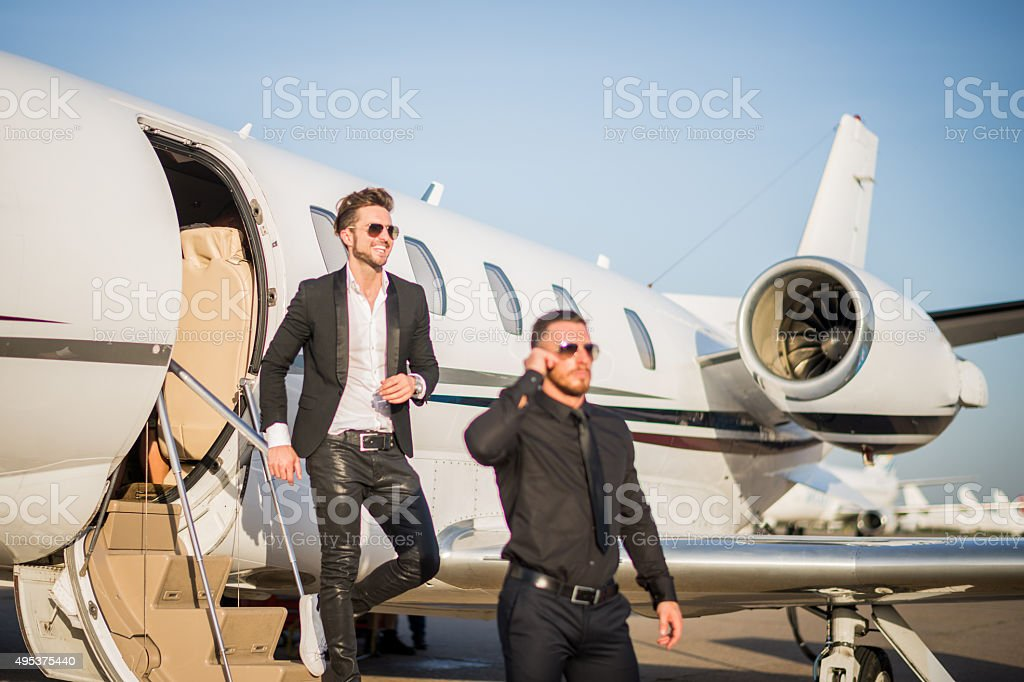 Famous person with bodyguard leaving the jet airplane stock photo