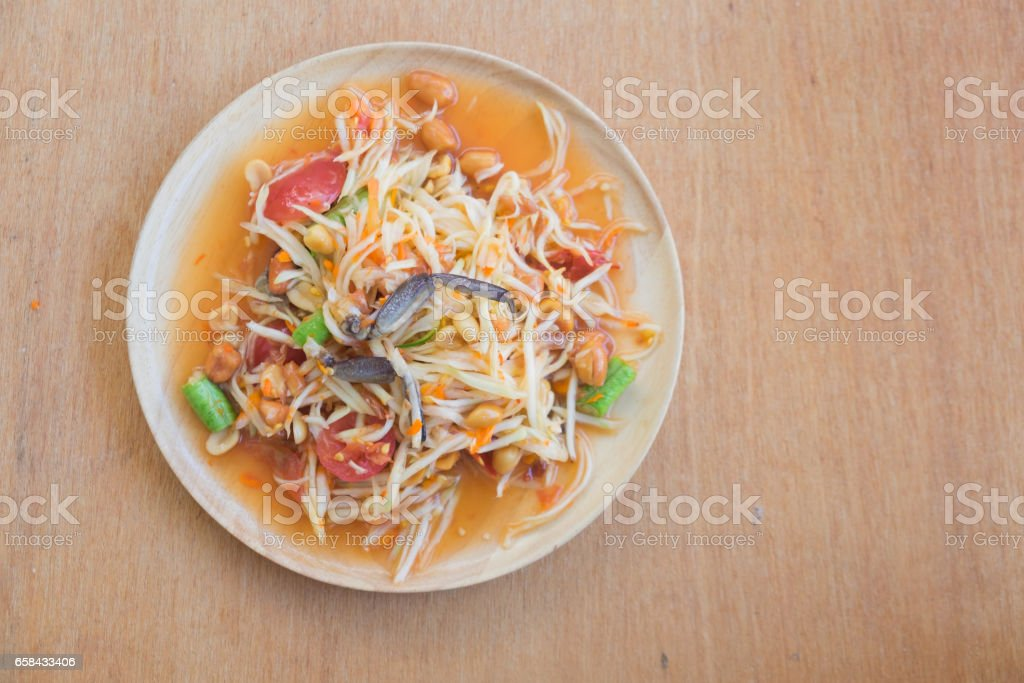 Famous Thai food. Papaya salad or what we called 'Somtum' in Thai on wood table. stock photo