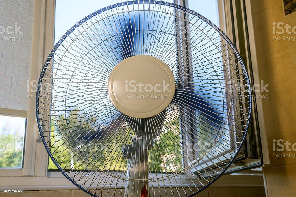 fan near an open window stock photo