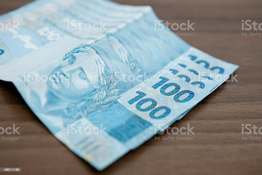 A fan of $100 Brazilian bills on a brown table stock photo