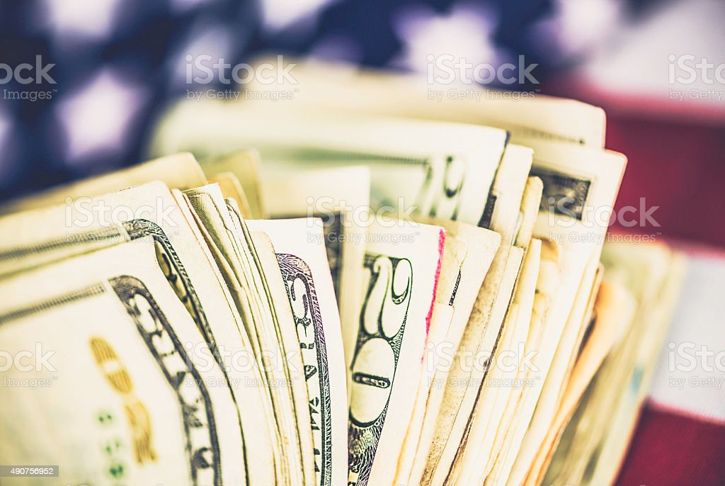 Fan of American twenty dollar bills against US flag stock photo