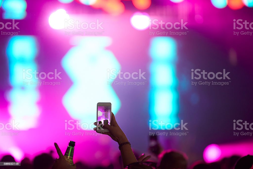 Fan Taking Photo On Mobile Phone At Music Festival stock photo