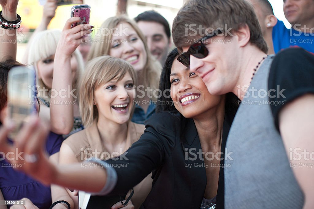 Fan taking picture of herself with celebrity stock photo