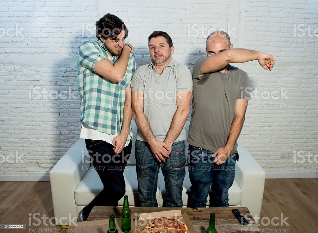 fanatic friends fans watching tv emulating football players in barrier stock photo