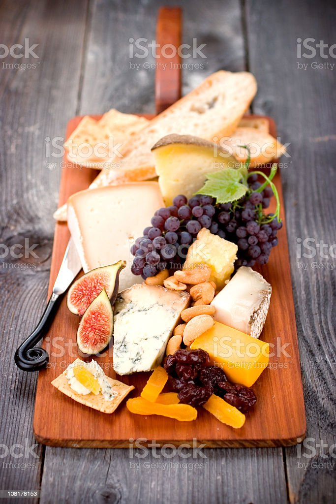 Fancy board of cheeses, figs, and grapes stock photo
