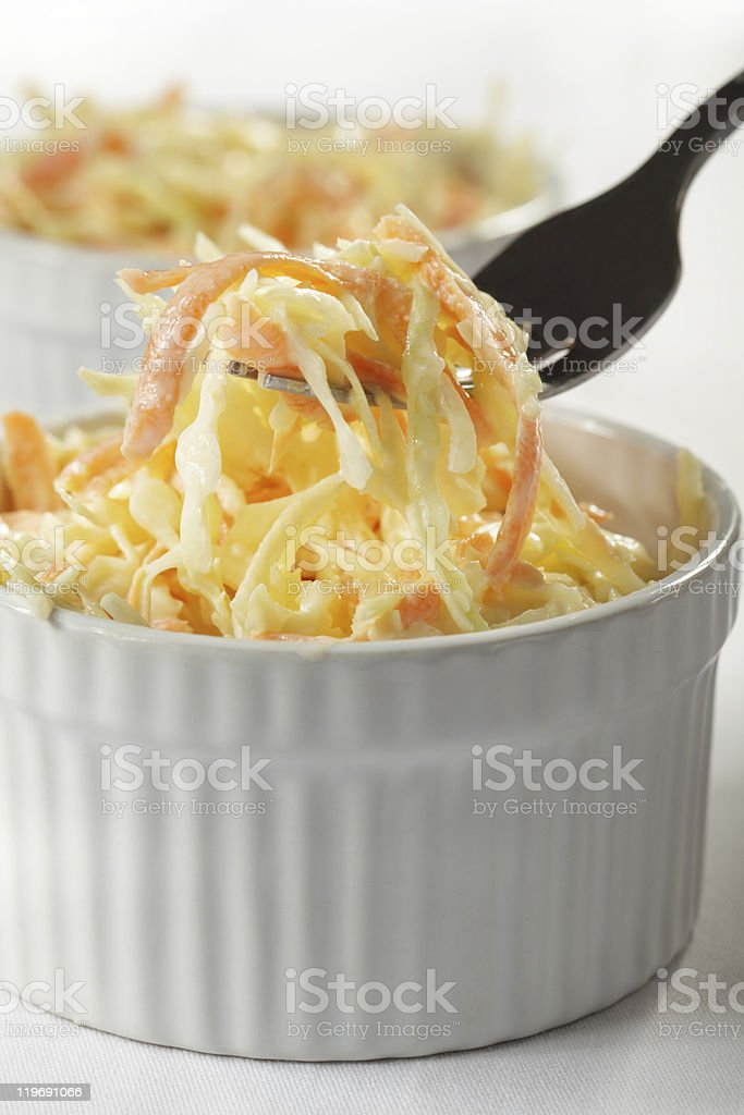 A fancy bowl of coleslaw with a fork removing some coleslaw stock photo