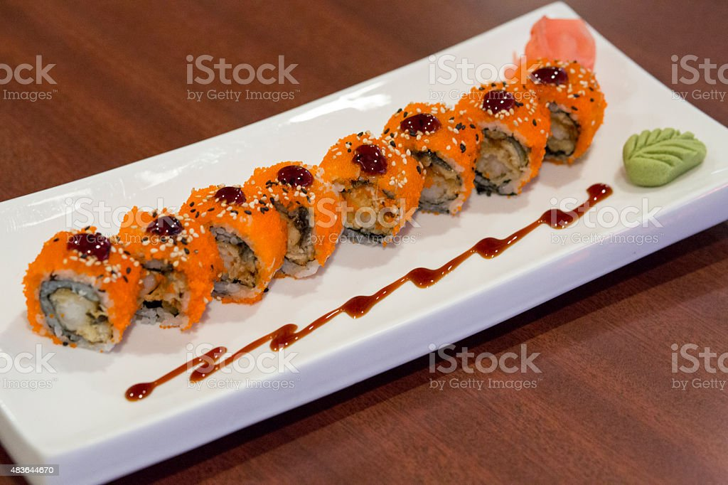 Fancy Dragon Sushi Roll with Wasabi Sauce on Wooden Table stock photo