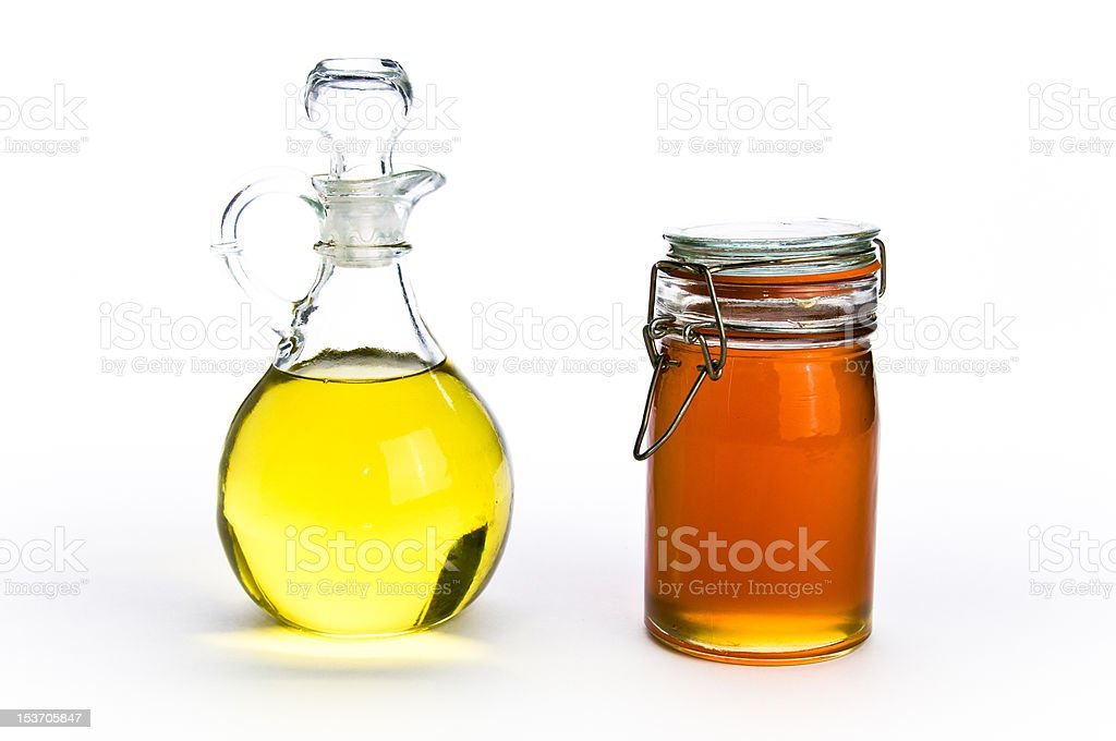 Fancy glass containers of oil and honey on isolating background royalty-free stock photo