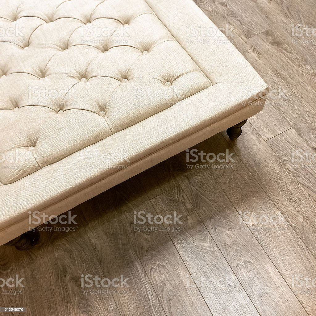 Fancy ottoman on wooden floor stock photo