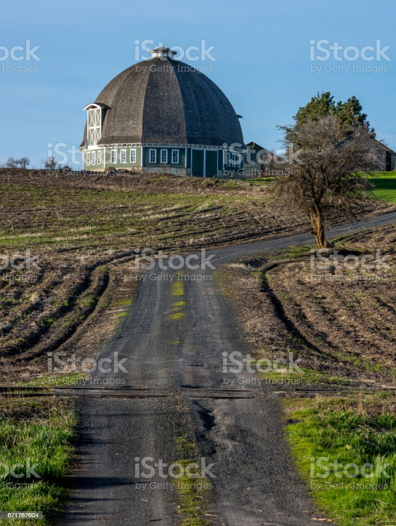 Fancy round barn with gravel road and tracks stock photo