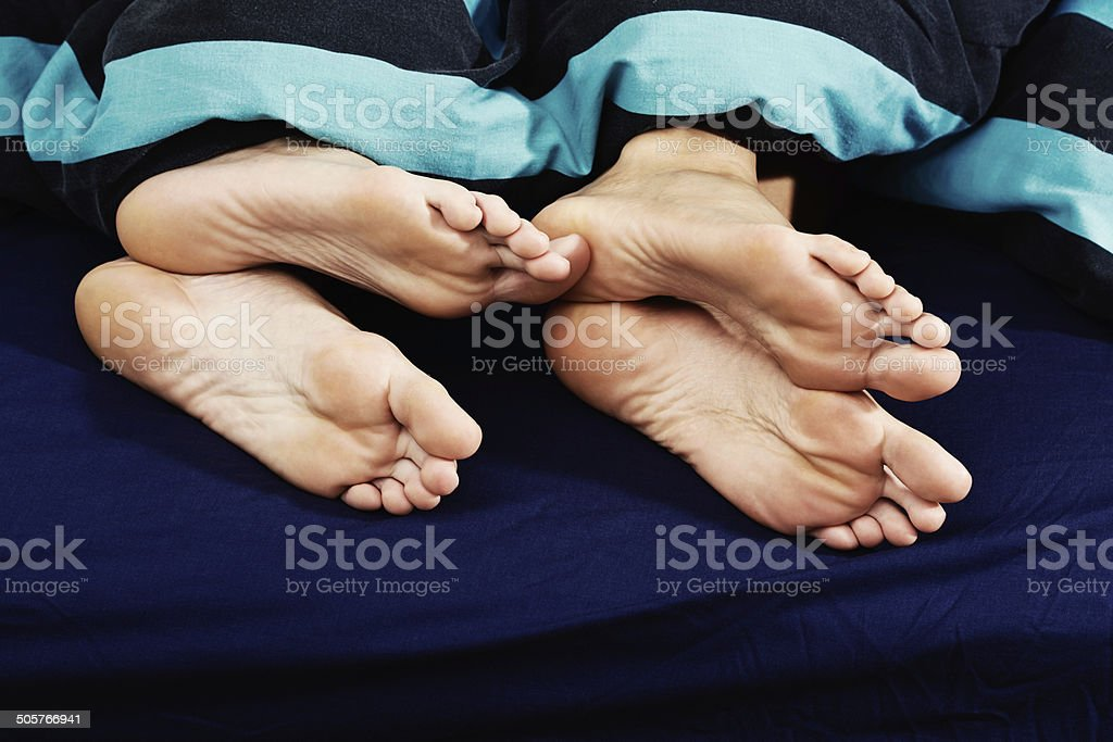 Fancy some action? Flirtatious feet in bed. stock photo
