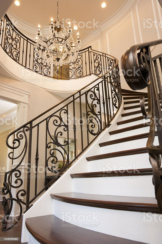 Fancy spiral staircase and traditional chandelier stock photo