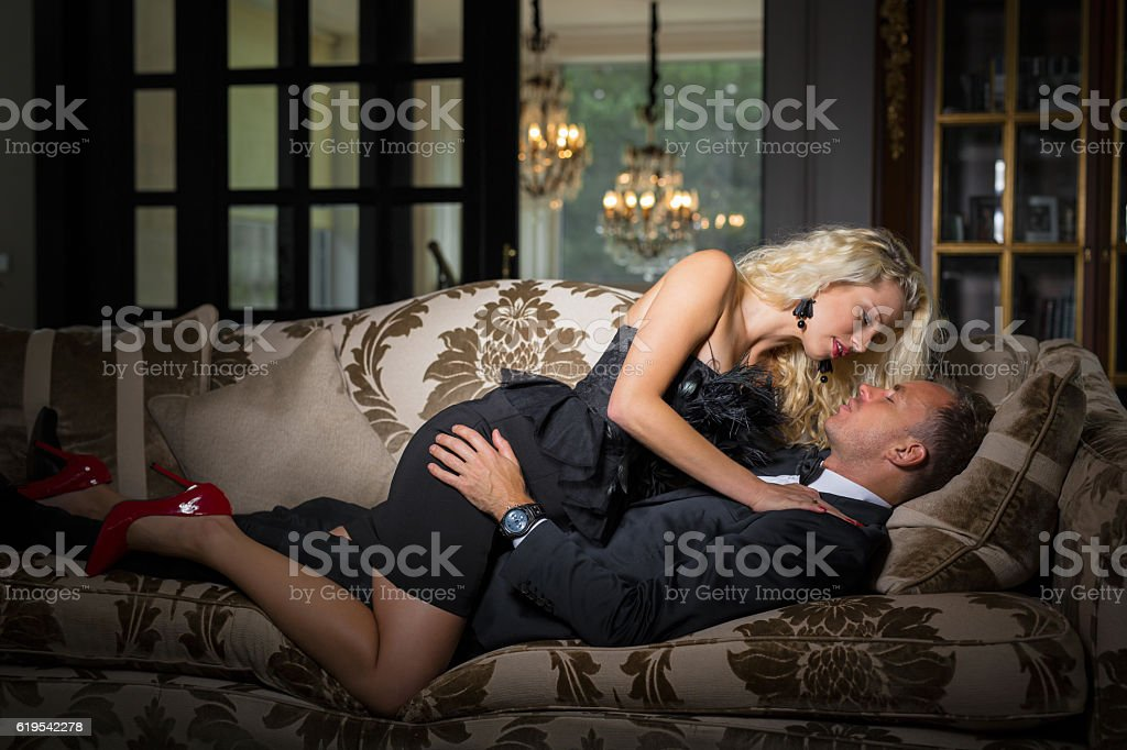 Fancy woman in black dress lying on top of man stock photo