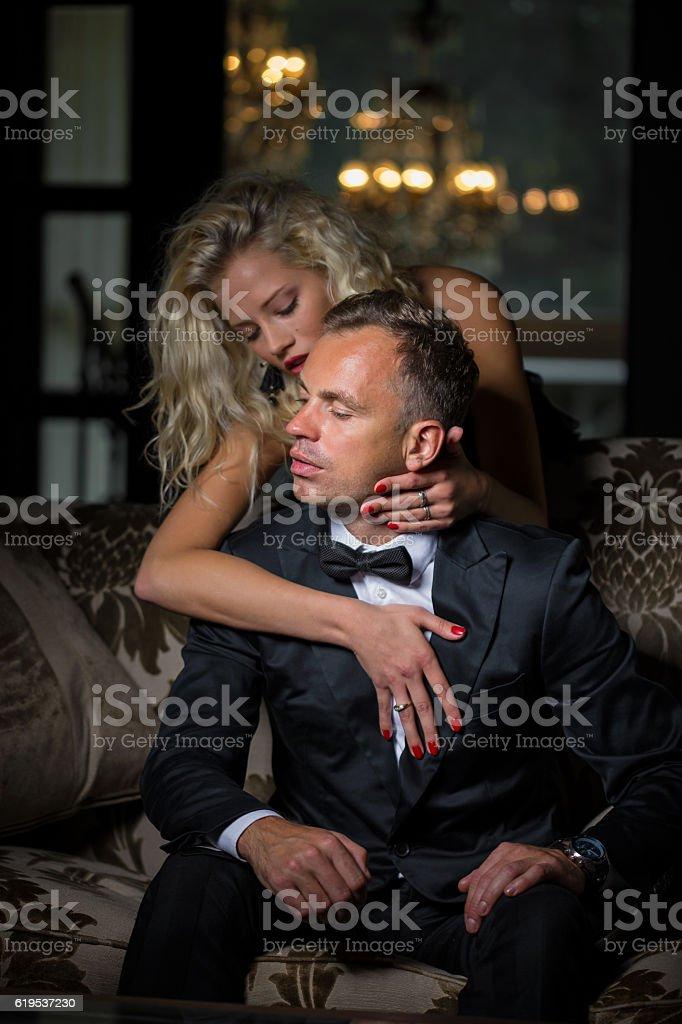 Fancy woman seducing man in black suit stock photo