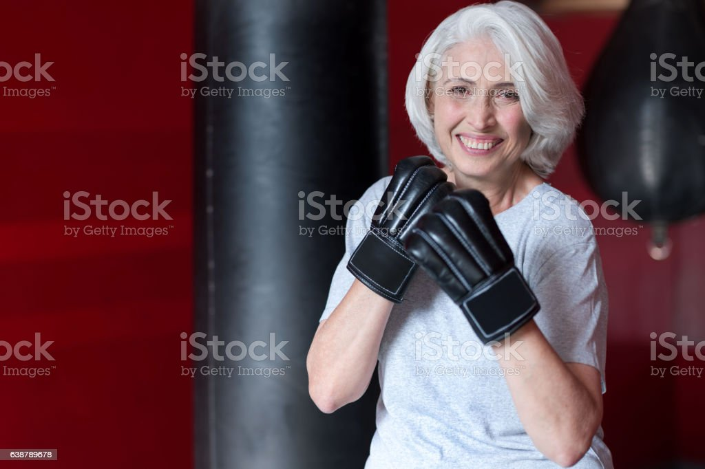 Fanny smiling gray haired woman preparing to boxing. stock photo