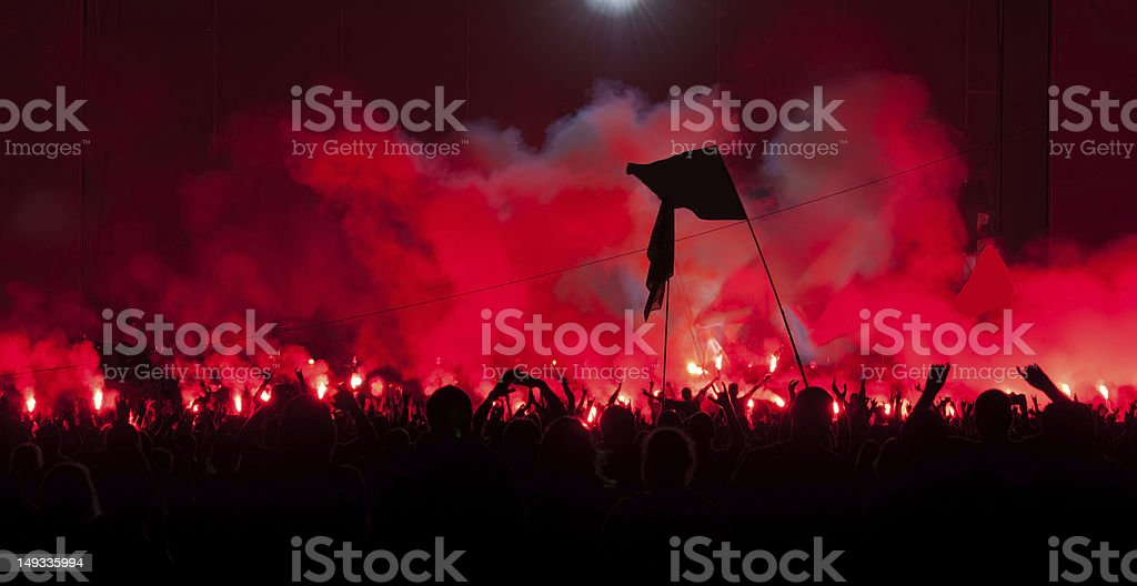 Fans burn red flares at rock concert royalty-free stock photo