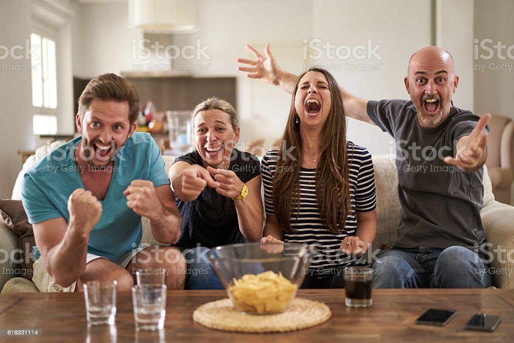 fans cheering at home stock photo