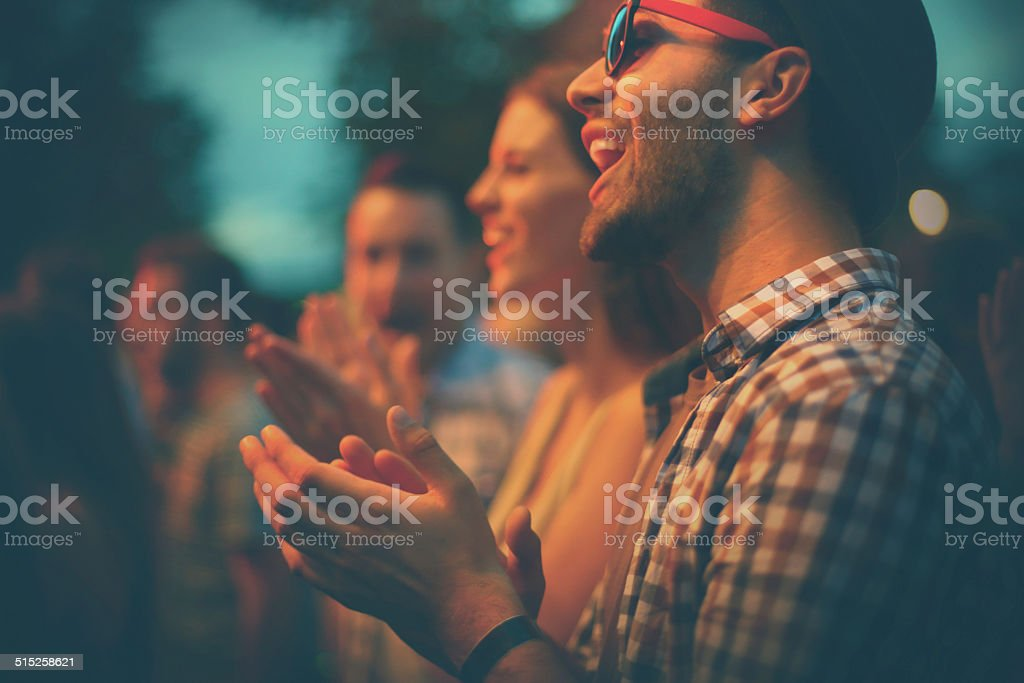 Fans clapping at concert. stock photo
