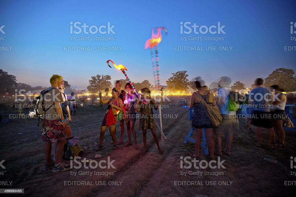 Fans holding Neon lights at dusk during music festival stock photo