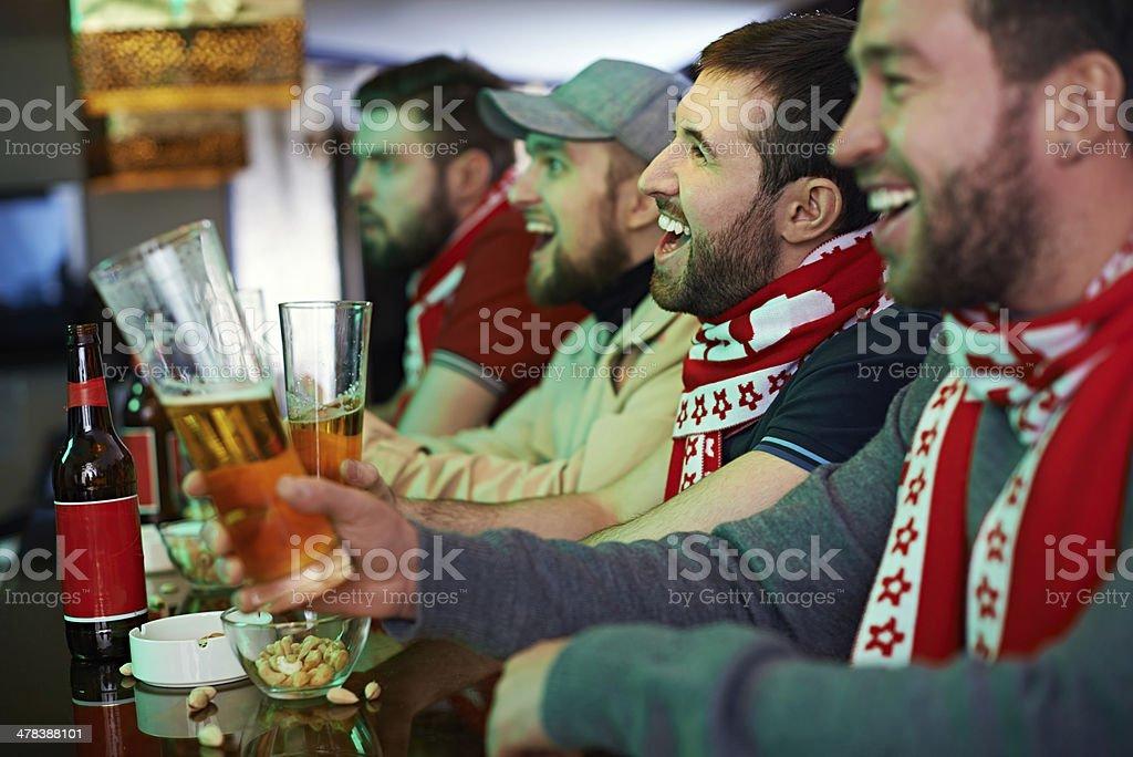 Football fans watching game at bar
